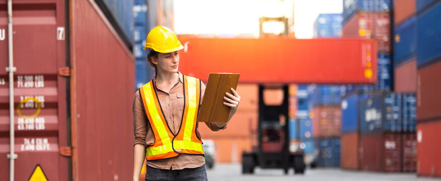 Portrait of Woman foreman worker use walkie talkie for control loading Containers box from Cargo at container yard. Import and Export concept. Marine, carrier and logistic insurance .