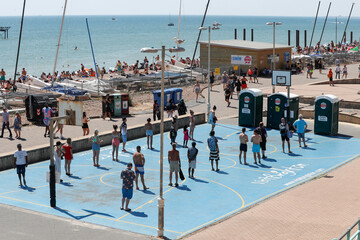 People queue in front of a public toilet on the beach, as the spread of the coronavirus disease (COVID-19) continues, in Brighton