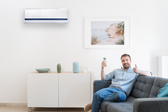 Happy guy cool down using air conditioning at home