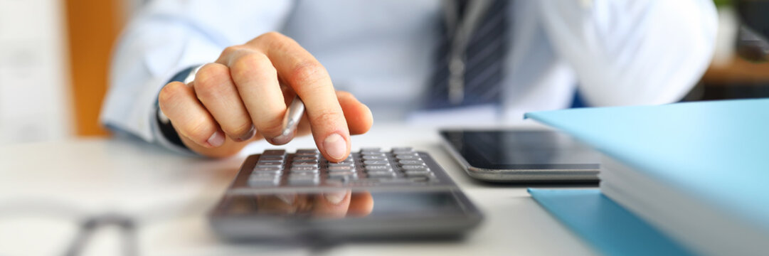 Manager counts on calculator sitting in the office