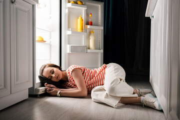 Young woman sleeping on floor near open fridge at night