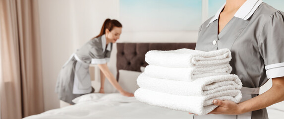 Chambermaid holding stack of fresh towels in hotel room, closeup view with space for text. Banner...
