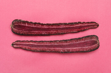Halves of raw purple carrot on pink background, flat lay