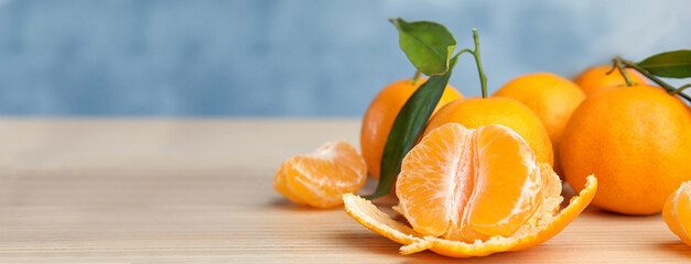 Fresh ripe tangerines with leaves on wooden table, space for text. Banner design