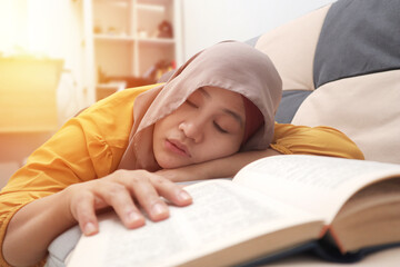 Beautiful Asian muslim woman slept while reading book on sofa, tired sleepy girl exhausted while...