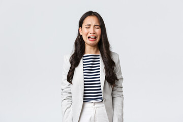 Business, finance and employment, female successful entrepreneurs concept. Uneasy distressed asian office lady feeling sad, crying and sobbing, standing depressed over white background