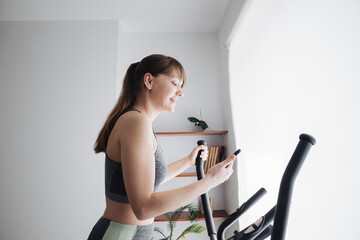 Woman using smartphone while performing workout on elliptical trainer at home