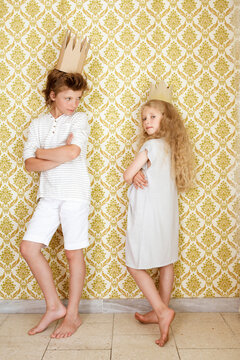 Boy and girl standing at a wall wearing cardboard crowns