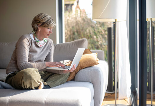 Woman using laptop while sitting on sofa in living room during working from home