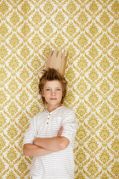 Portrait of a boy standing at a wall wearing cardboard crown