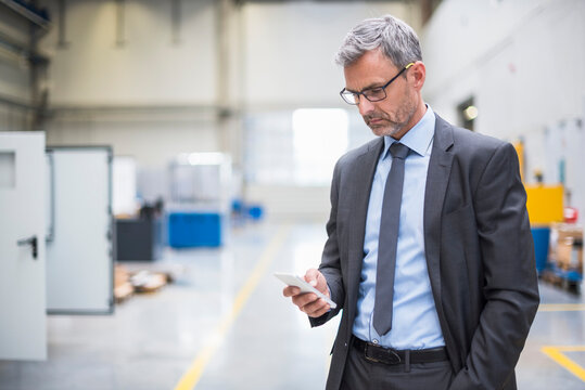 Mature businessman using cell phone in a factory