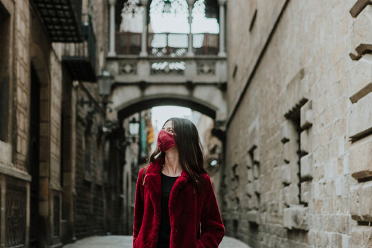 Woman wearing face mask looking away while standing on empty alley of Gothic Quarter during quarantine, Barcelona, Spain