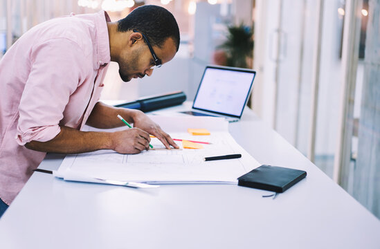 Male student architect in eyewear concentrated on blueprint drawing preparing coursework project using laptop computer and wireless connection to fast 4G internet in university modern library