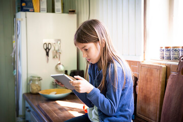Girl sitting on worktop in the kitchen looking at digital tablet