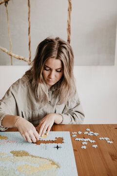 Woman playing with puzzle at table during home quarantine
