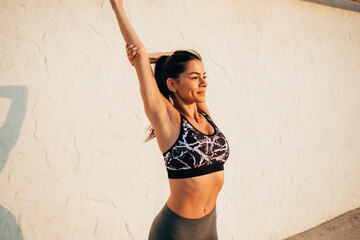 Confident young female athlete stretching on promenade during sunny day