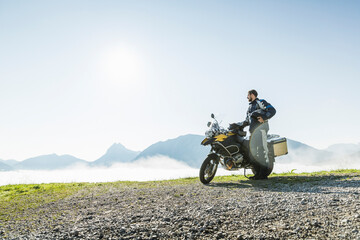 Motorcyclist on a trip having a break in the mountains, Achenkirch, Austria