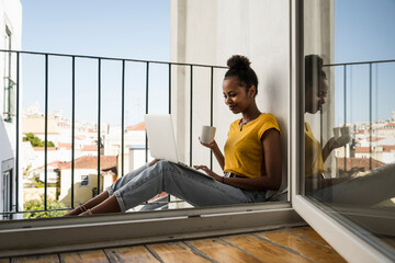 Young woman sitting on a balcony with laptop and coffee cup