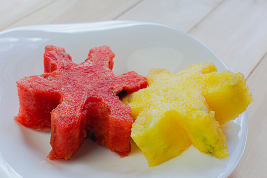 Close-up pieces of star shape red watermelon and yellow melon on a white ceramic plate on wood table