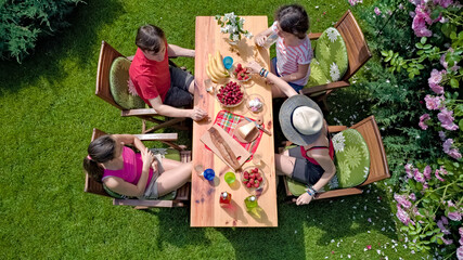 Family and friends eating together outdoors on summer garden party. Aerial view from above. Leisure, holidays and picnic concept