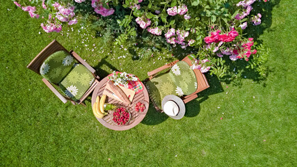 Decorated table with bread, strawberry and fruits in beautiful rose garden, aerial top view of romantic date table food setting for two from above