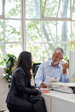 Mature aged male office worker meeting with a woman in a creative warehouse space