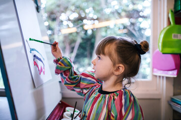 Preschool girl painting a picture