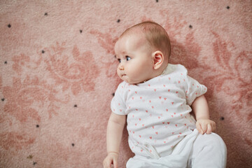 6-month old baby girl enjoying lying on pink carpet