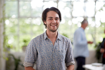 Young professional man standing in an open plan office