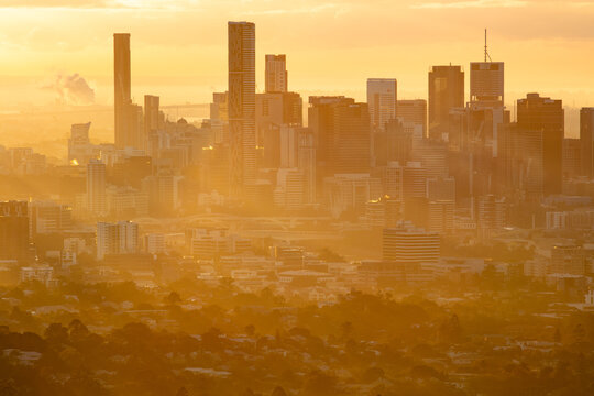 Brisbane city skyline with golden colours of the rising sun reflecting off cool morning fog