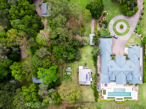 Top down aerial view of luxury homes beside small original house