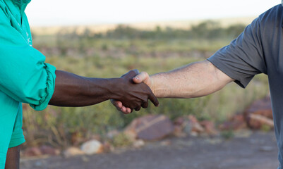 Two men shaking hands in the outback