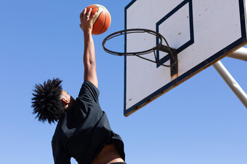Basketball hoop with young guy about to slam a goal