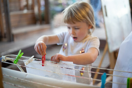Child carefully pegs a painting to dry at preschool