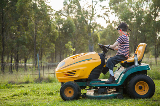 Kid mowing the backyard on a ride on lawn mower