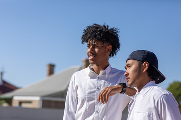 two teenage boys in white shirts looking off camera