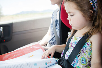 Young girl reading a book in the car