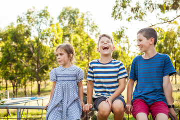 Three happy children laughing together outside