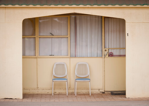 Chairs outside a pale yellow motel room on the Nullarbor