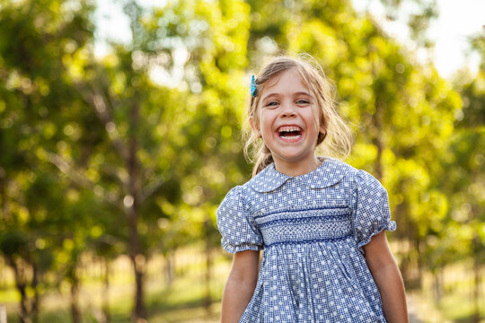 Happy young girl laughing outside wearing dress