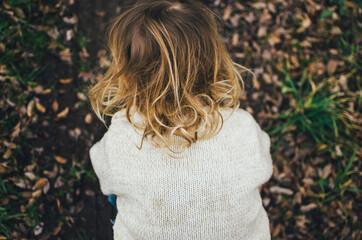 Little girl outside in garden with blonde curls