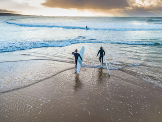 Two surfers walking into the ocean at sunrise