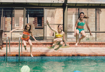 Three girls jumping into a swimming pool