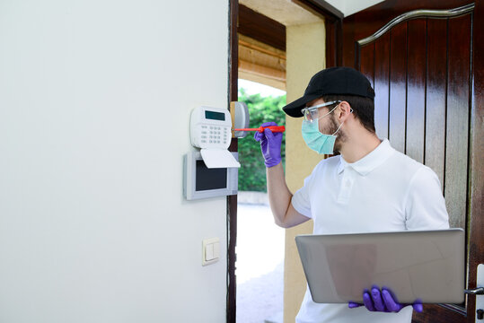 handsome young man installing anti burglary alarm at a client house with a surgical mask and gloves during pandemic period
