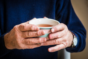 Elderly hands holding a warm cup of tea