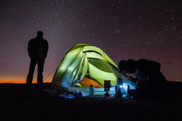 Two men silhouetted with tent camping under the stars