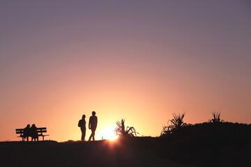 Silhouettes walking at sunset
