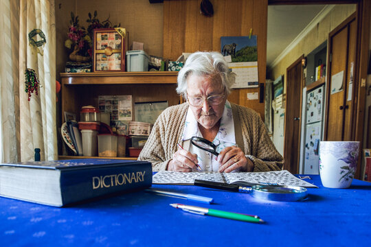 Senior woman solving crossword puzzle with dictionary and magnifying glass