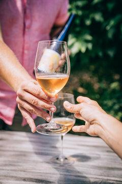 Man handing glass of wine to woman