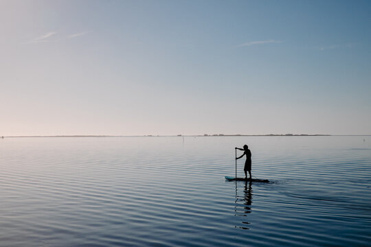Silhouette of a person on a stand-up paddle board of calm water